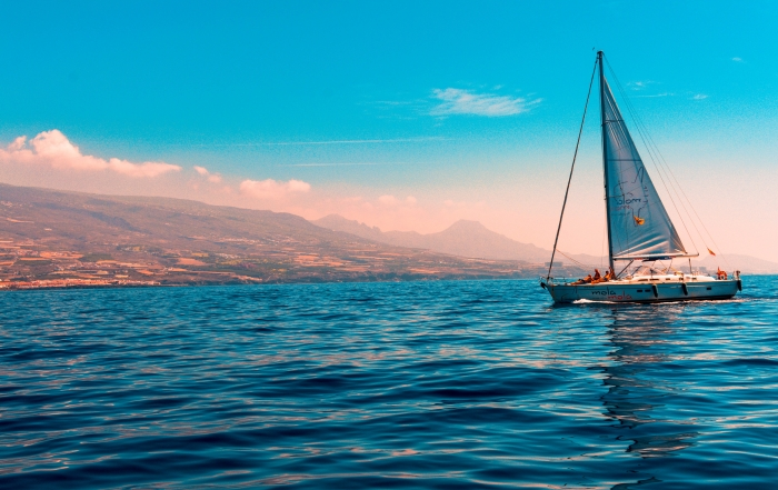 sailboat-sailing-on-water-near-island